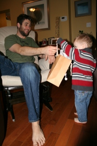 Christmas morning, trying to convince Henry to pull the toy out of the bag.