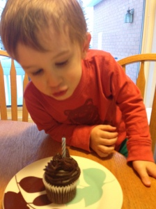 Henry got a little cupcake after dinner which he savoured very slowly
