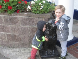 "The boys giving their traditional morning hug to the ""black dog"" outside the ""black dog pub"""